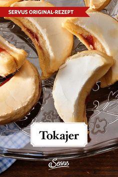 Diese kleinen Kekse sind durch den luftigen Teig, die süße Marmelade und die leichte Glasur meistens schnell wieder weg. #tokajer #kekse #plätzchen #keksrezepte #plätzchenrezepte #rezept #rezeptideen #weihnachtskekse #weihnachtsplätzchen #keksebacken #plätzchenbacken #weihnachtsbäckerei #servus #servusmagazin #servusinstadtundland