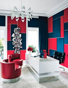 Mod home office with a blue and red theme, a large fur rug, and mod red chairs