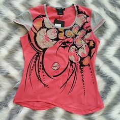 """🆕 Glamorous Urban Chic top NWT Brand new with tags  Glamorous Urban chic top! Different textures and multi colored rhinestones on a salmon pink background make this top a smashing success! Pair with leggings & boots or shorts & sandals! Black texture is velvet-like to the touch. Bottom of shirts waves up and down, adding a touch of sexiness. (Seen in pics)  100%cotton  Length to lowest points approx 23.5"""" Bust side to side 18"""" Colors of gray, black, tan, blue, red, salmon pink etc.  💗PRICE…"""