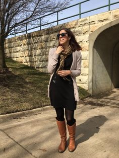 Tan cardigan with brown riding boots, leopard print scarf and a black dress