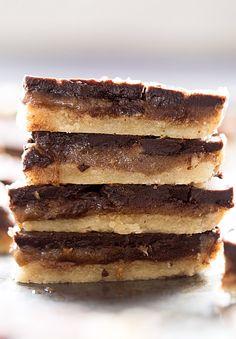 Wholesome Caramel Chocolate Shortbread Bars: chewy shortbread crust, rich caramel filling, and creamy chocolate. Grain free, sugar free, vegan! Video included.   TrufflesandTrends.com