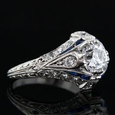 This is a stunning, original Art Deco diamond engagement ring from the early 20th century. A 1.07 carat antique cushion cut diamond is set in this highly decorative mounting set with both sapphires and diamonds.