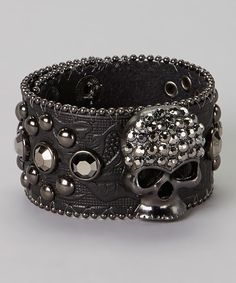Bare wrists need a pop of punkish glam? Artfully embossed leather, hematite beads and a rhinestone-studded skull make this snap bracelet the perfect pick for edgy elegance.