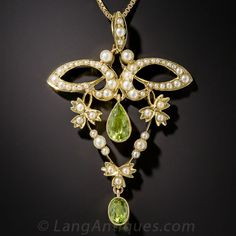 Art Nouveau Peridot and Seed Pearl Pendant Necklace. From turn-of-the-twentieth century Great Britain comes this thoroughly enchanting Art Nouveau necklace. The pendant features a pair of glistening lime green peridots dangling inside and below a classic whiplash motif studded with shimmering seed pearls. The 2 inch long pendant is 15ct. gold, the 20 inch necklace is 9ct. gold