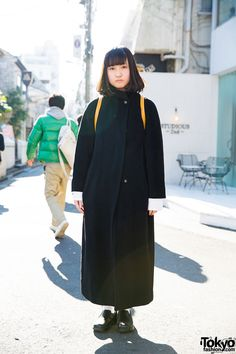 16-year-old Rune on the street in Harajuku wearing a minimalist style featuring a Max Mara maxi coat, a yellow Loewe backpack, and vintage loafers from Sankaku. Full Look