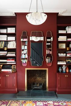 Red living room with oxblood paint, unusual mirrors and bookshelves