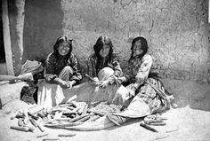 Portrait of unidentified Native American women (Hopi) wearing print fabrics and sitting by a pile of corn. - Matteson - 1899/1900