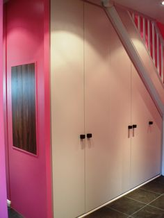 Under stairs storage cupboards / pink wall with key cupboard