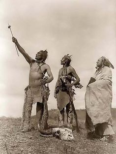 Here for your enjoyment is an inspiring photograph of a Crow Indian Oath. It was made in 1908 by Edward S. Curtis.  The photo illustrates Three Crow (Apsaroke) men gazing towards the sky, with two of them holding Winchester rifles> One of the Indians has an object skewered on his arrow, with the arrow pointed skyward. There is a bison skull sitting at their feet.    We have compiled this collection of photos mainly to serve as a vital educational resource. Contact curator@old-picture.com.