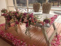 top table, long and low arrangement. this would cost a lot to have so many roses, although if its a look you really want, we could look at cheaper flowers.. ie if you used mainly iris and the blue tweedia type flower, or wax flower / gypsophila