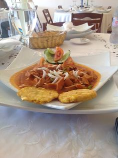 Lambi (conch) in sauce creole with fried plantains