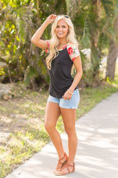 This gorgeous floral blouse will have you dreaming of warm California days! Featuring a classic black color paired with a lovely floral print in fuchsia, green, hot pink, cream, orange, yellow, and pi