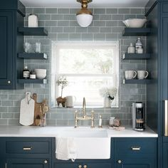 Our Beach House Kitchen: The Reveal - check out this kitchen inspiration from our New York kitchen with two tone cabinets, the first color is a navy blue with brass hardware (file box pulls) and brass vintage style faucets with farmhouse sink. The green grey subway tile with white grout pair perfectly with the open shelves. #remodelingonabudget