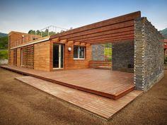 Terrasse basse et faux toit en poutre de bois. La pierre est magnifique.