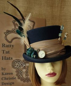 Navy blue ladies Steampunk top hat with antique gold slubby silk band, ladies pocket watch, blue peony flowers, coordinating hatpins and feathers.