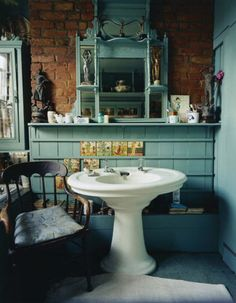 love the pedestal sink. the colors of the terracotta looking brick wall and greenish paint are excellent.