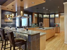 This beautiful kitchen blends two-toned cabinets with a variety of stone types to create a warm, inviting space. It also provides plenty of functional space, with a large island and acres of granite countertops.