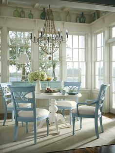breakfast nook....love the shelf above the windows with recycled glass bottles, painted chairs, chandelier...its a lovely space!!