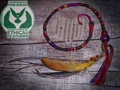 DRUMMER GIRL Feathered HairWrap - Warm shades of brown and burnt orange, with a hint of red and purple. And just a touch of brown glitter thread to add depth. With purple and dark wooden beads. With a detachable Bronze effect (antique gold style) hand made seed bead dangle charm on the end. With CRUELTY-FREE chicken feathers (one that I have hand dyed), and peacock barbs.  The charm is removable and interchangeable. For added durability, my charms are always fitted to split rings, not the…