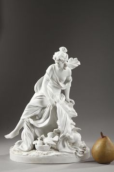 A group in porcelain biscuit representing an allegorical scene with a woman dressed with a floating drapery, sitting on a rock and discovering Cupid. Knelt down at her feet...