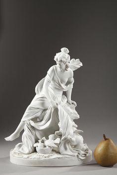 Un groupe en biscuit de porcelaine, modèle de Sèvres figurant une femme couverte d'une draperie flottante, assise sur un rocher et découvrant Amour. Agenouillé à ses pieds, ce dernier...