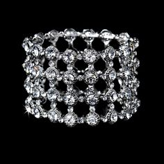 "Bracelet.  A Modern and stylish silver plated bracelet is encrusted with clear rhinestones and crystals in a geometric pattern. A perfect accessory for your homecoming, prom or wedding day. This bracelet will stretch to fit most wrists and is 1 1/2"" in width."