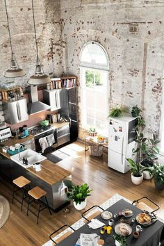 paredes decoradas, cocina abierta con isla fotografiada desde arriba, ventana grande alta, paredes de ladrillo con efecto desgastado