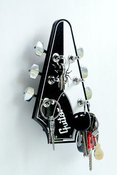 Hello guitar lovers!!!! Turn some heads with this amazing looking key holder. Designed in the style of a Flying V, one of the most iconic and easily recognized guitars ever made!!! The face of the rack is made from two tone acrylic with a wood back and comes with actual chrome guitar tuning pegs that just adds a fantastic look of realism to a unique key holder. Can be ordered either in the two tone black and white or all black. Guitar gunslingers, metal maniacs and axe wielding guitar…