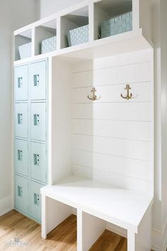 White cottage mudroom stands out with Tiffany blue accents and features four rows of stacked Tiffany blue lockers positioned under overhead shelves holding Tiffany blue baskets above a white built in bench fixed against a shiplap trim accented with brass anchor hooks.