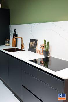 Zwarte greeploze keuken met aanrechtblad van marmer.