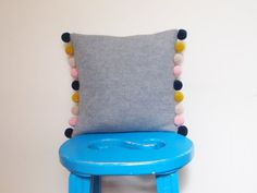 The cushion is out of stock at the moment but can be made to order.  This new mini pom pom cushion is knitted on my hand powered knitting machine with 100% soft lambswool.  The cushion is grey with navy, golden yellow, beige and pink pom poms.  The pom poms are made by me using the same lambswool that the cushion is made with.  Size is 25 x 25 cm - 10 x 10 in  Comes with a duck feather pad.