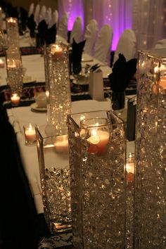 tall vases with sparkle and a candle in them. cute and simple. could be nice on sweets tables, or in cocktail hour, or on the ledges in the windows. tons of possibilities