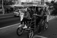 Family riding a four wheeled bike at the seaside promenade of Nice in the south of France. Sitting at the front, the youngest is holing a doll and yelling out loud. Street Pictures, South Of France, Baby Strollers, Baby Prams, Prams, Strollers