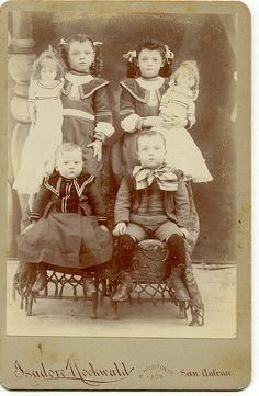 Four posed siblings - Two in matching outfits are holding their favorite dolls.  - (by twm1340, via Flickr)