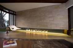 Long, linear fireplace set in stone on the ground is sleek and intriguing.
