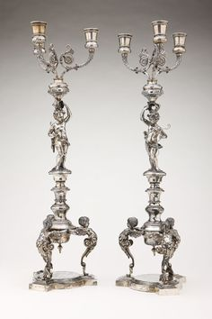 A pair of German silver 3-light candelabra, Hanau, Circa 1890, each with marks to base and column for Hanauer Silberwaren Manufaktur, .835 standard silver, each depicting a cupid holding aloft three leaf-clad candlearms with vase form sockets and standing on a knopped column supported by three winged putto-form monopodiae.