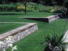 Grass walkway with pretty stone wall, landscape design by HMWhite