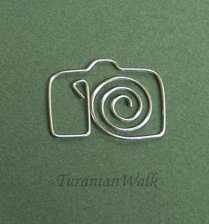 Camera bookmark by my own design.    Size: 3 cm    These bookmarks are made by hand from 18 gauge soft silver plated wire. Before carefully formatting I roll them to get a right firmness.  I don't use any patterns, so all of my creations are unique.    Take a look at my sales and if you have a request just send a message and I'll make it !  Also, if you have any questions ask them before buying. Please dont hesitate to contact me.