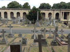 View of the numerous tombs along Center Avenue leading to the central roundrel of Brompton Cemetery, London, England.  Below the colonnades are catacombs which were originally conceived as a cheaper alternative burial to having a plot in the grounds of the cemetery. Unfortunately, the catacombs were not a success and only about 500 of the many thousands of places in them were sold.