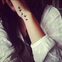 Side-of-hand bird tattoo