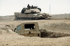 M1A1 Abrams main battle tank with mine plow passing by ruined Iraqi truck.
