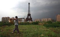 A farmer carrying a rake walks down a dirt road past a replica of the Eiffel Tower at the Tianducheng development area in Hangzhou, Zhejiang Province. Tianducheng, developed by Zhejiang Guangsha Co Ltd, started construction in 2007 and was known as a knockoff of Paris with a scaled replica of the Eiffel Tower standing at (354 ft) and Parisian houses. Although designed to accommodate at least 10 thousand people, Tianducheng remains sparsely populated and is now considered as a 'ghost town'.