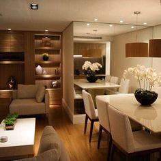 """""""Uma sala muito linda que teve o seu espaço ampliado com a utilização de uma parede de espelho que foi realçada pela iluminação. O piso em réguas de…"""""""