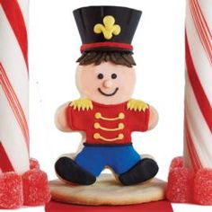 A great toy soldier stands guard on your holiday dessert table. Every detail on his uniform is crisply detailed with royal icing. Set on a round cookie base, he can be used as a place setting populated a wonderful dessert table.