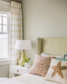 Citrus tones in the guest bedroom create a fresh feel. Multiple patterns, including a green Galbraith & Paul geometric fabric on the headboard and striped Larsen drapery fabric, are expertly mixed for a layered look. Next to the bed is a bottleneck glass table lamp with swirls of moss green and yellow from Arteriors.
