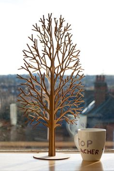 Tree #3 with an elegant delicate details is a laser cut set of two MDF wood panels which slot together to stand free on a desk, a shelf or mantelpiece at home or at work. These panels are 290x450mm each and could be a center piece in any room. The laser cutting process can leaves a