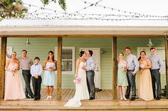 A wedding party in mismatched pastel attire gathered on the venue's porch for a summer backyard wedding ceremony in Florida.