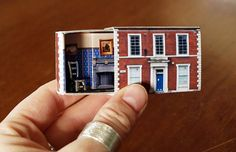 A regular matchbox is given a makeover to become a cute little house that can fit in your hand. Photographs cover the box and metal furniture is inside. Chair style may vary slightly from pictured.  Measures 5.4cm wide, 3.7cm tall and 1.7cm deep when closed. A lot of love has gone into the making of our dollhouses and each is a totally unique upcycled piece. They are significantly handmade and as such have their own personality and imperfections. Young people should be supervised and care…