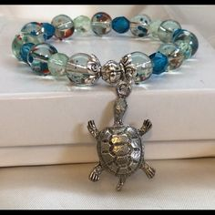 """Limited edition sea turtle bracelet NWOT Limited edition fire and rain turtle charm stretch bracelet. Features 10mm seasonal glass beads fire and rain and 8mm Czech fire-polished beads in green and blue. All strung on stretch cord and reinforced 3x for durability. Finished off with a silver toned sea turtle charm. So cute a must have add to your collection of bracelet stacks. Will fit a women's wrist of 7-8"""" Handmade Jewelry Bracelets"""
