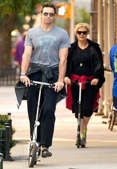 We think it's too funny that Hugh Jackman and his wife Deborra-Lee Furness ride scooters around NYC! Of course, they do it in shady style!